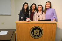 Four young Asian American/Pacific Islander student nurses smile at the camera