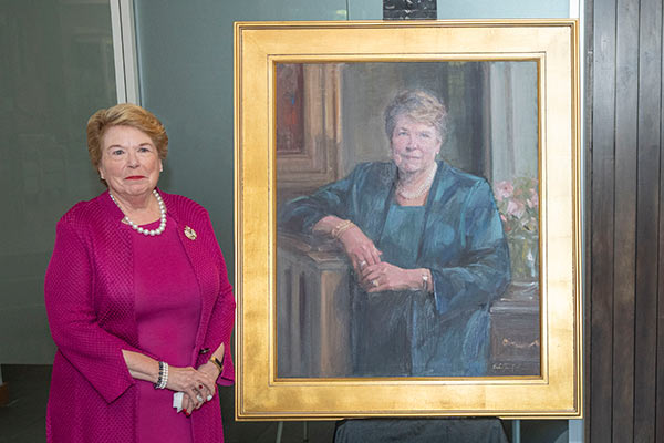 Dean Linda Norman stands next to an oil portrait of herself