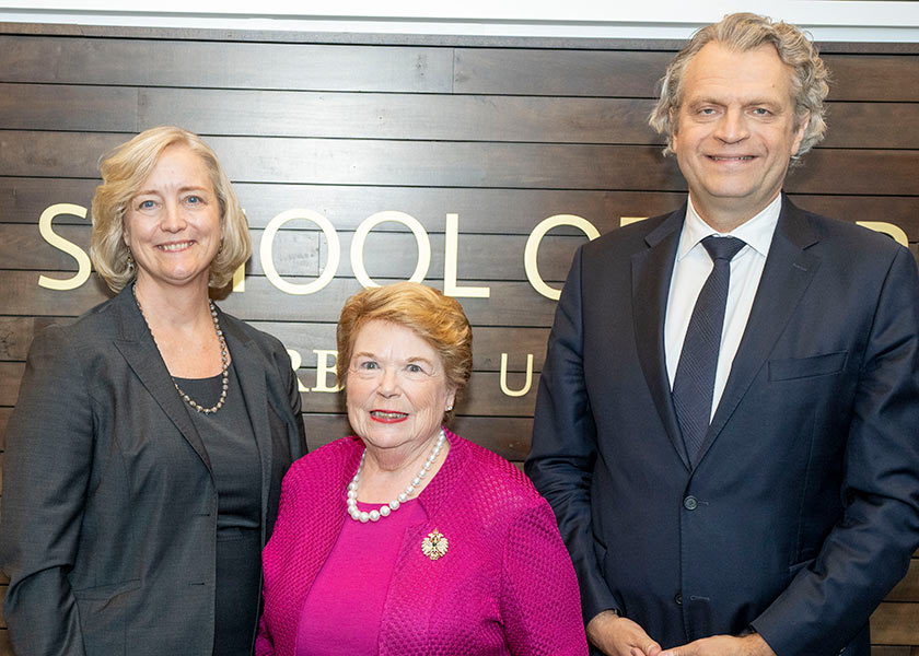 Provost Wente, Dean Linda Norman and Chancellor Daniel Dermeier pose in front of a wood wall that says School of Nursing